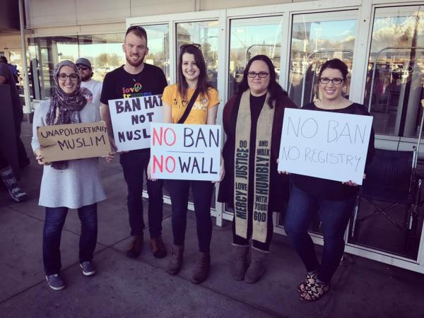 """Here is Abigail Clauhs with members of her church holding up signs that say, """"No Ban; No Wall""""""""; """"No Registry"""" and """"Unapologetic Muslim."""""""