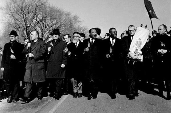 Rabbi Abraham Joshua Heschel guides Dr. Martin Luther King Jr. in the 1965 March on Selma.  In fact, there are only two black men in the picture.