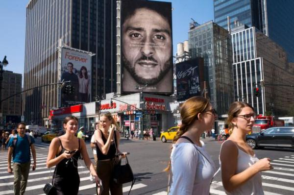 People walk by a Nike advertisement featuring Colin Kaepernick.
