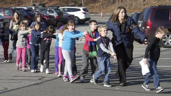 Cropped photograph taken by Shannon Hicks, police and teachers lead children away from Sandy Hook Elementary on Friday, Dec. 14.