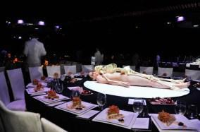 Performance actors in training lying naked under plastic skeletons revolving on the $100,000 dinner tables.