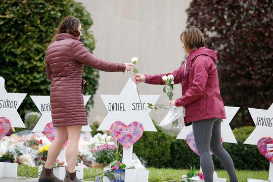 Two women place flowers outside of the Tree of Life Congregation Synagogue